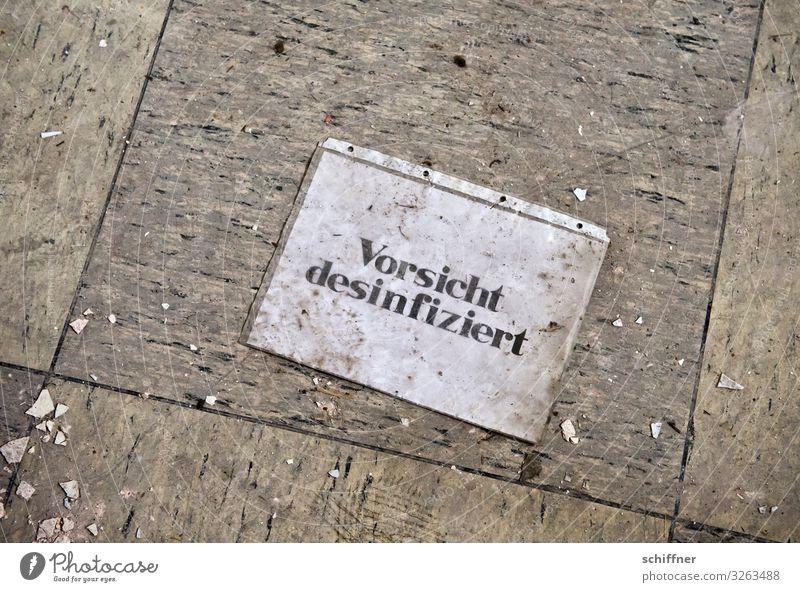 Lüge Schriftzeichen Hinweisschild Warnschild dreckig Bodenbelag Bodenplatten bodennah Desinfektion Vorsicht Warnung lügen unlogisch Klarsichtfolie Müll seltsam