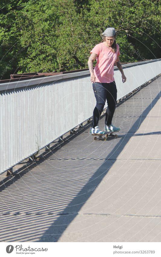sportliche Dame fährt mit dem Scateboard auf eine Brücke, das Geländer wirft Schatten Sport Fitness Sport-Training Skateboard Mensch feminin Frau Erwachsene 1