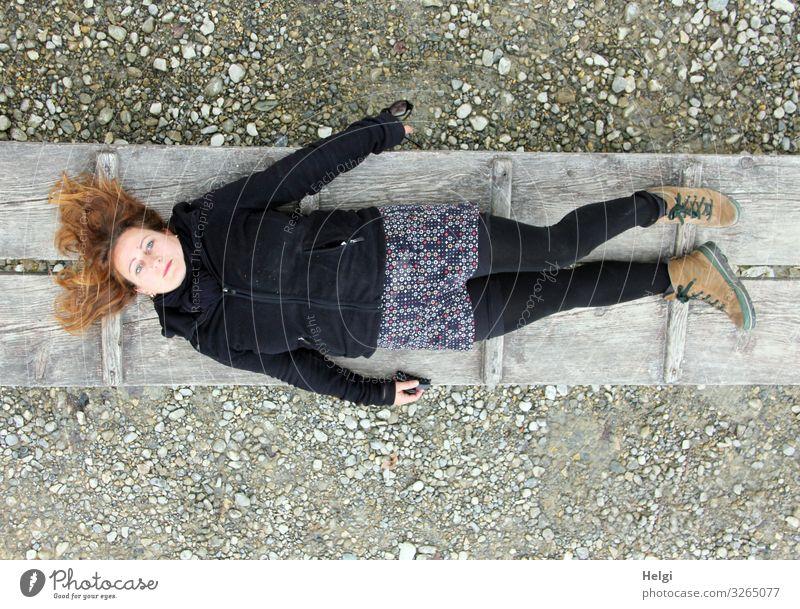Frau mit langen brünetten Haaren und dunkler und gemusterter Kleidung liegt auf einem Holzsteg Mensch feminin Erwachsene 1 45-60 Jahre Erde Frühling Bekleidung