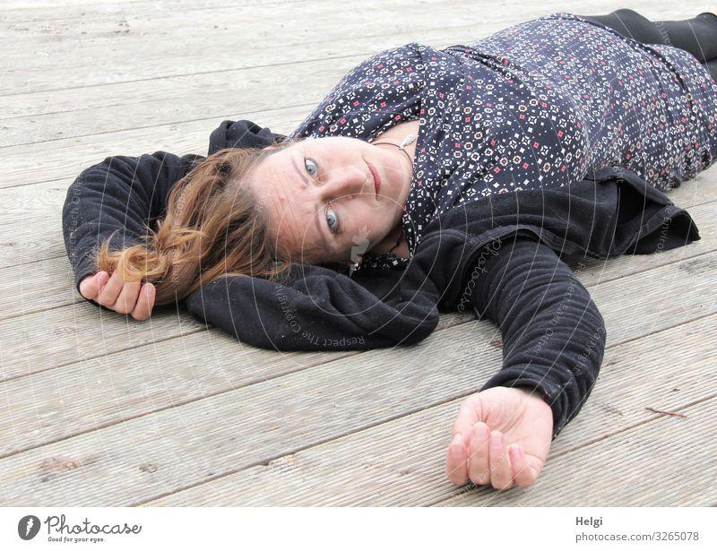 Frau mit langen brünetten Haaren und dunkler und gemusterter Kleidung liegt auf einem Holzboden Mensch feminin Erwachsene 1 45-60 Jahre Bekleidung Jacke