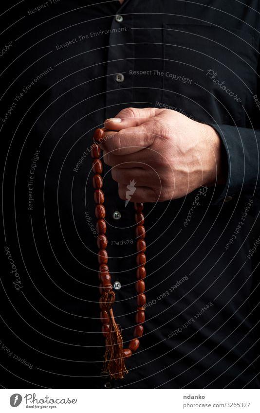 Mann im schwarzen Hemd hält einen Rosenkranz aus braunen Steinen Meditation Mensch Erwachsene Arme Hand Finger Kultur Vertrauen Hoffnung Religion & Glaube