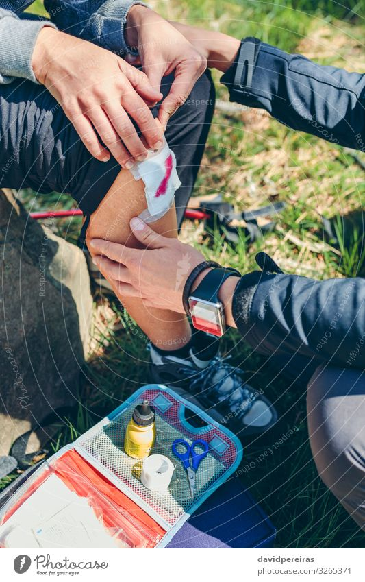 Mann heilt beim Trekking verletztes Knie einer Frau Lifestyle Berge u. Gebirge wandern Schere Mensch Erwachsene Paar Natur Herbst Wald sitzen authentisch Wunde