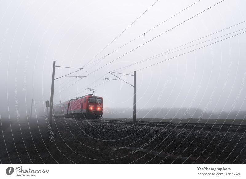 Rote Zuglokomotive durch Nebel, der sich auf Eisenbahngleisen bewegt. Ferien & Urlaub & Reisen Ausflug Winter Herbst schlechtes Wetter Verkehr