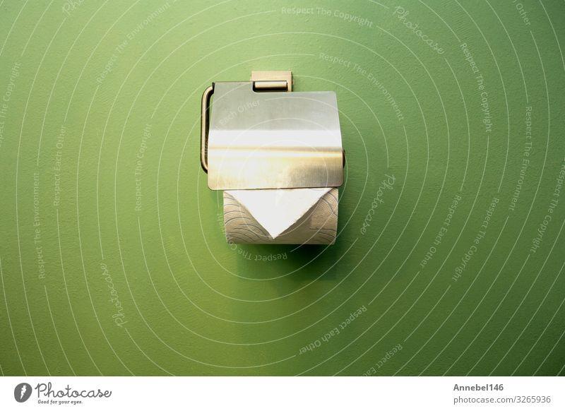 Nahaufnahme des WC-Papierhalters im Bad nahe der grünen Wand Design Accessoire Metall glänzend modern neu Sauberkeit weich weiß Toilette rollen Klammer sanitär