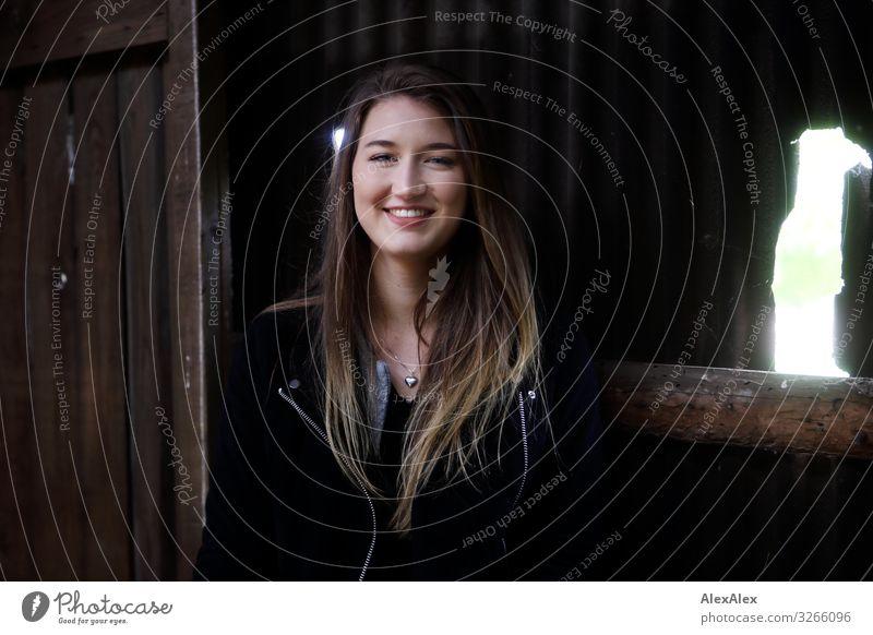 Portrait einer jungen lächelnden Frau vor einem Schuppen Stil Freude schön Leben Wohlgefühl Scheunentor Junge Frau Jugendliche 18-30 Jahre Erwachsene Landschaft
