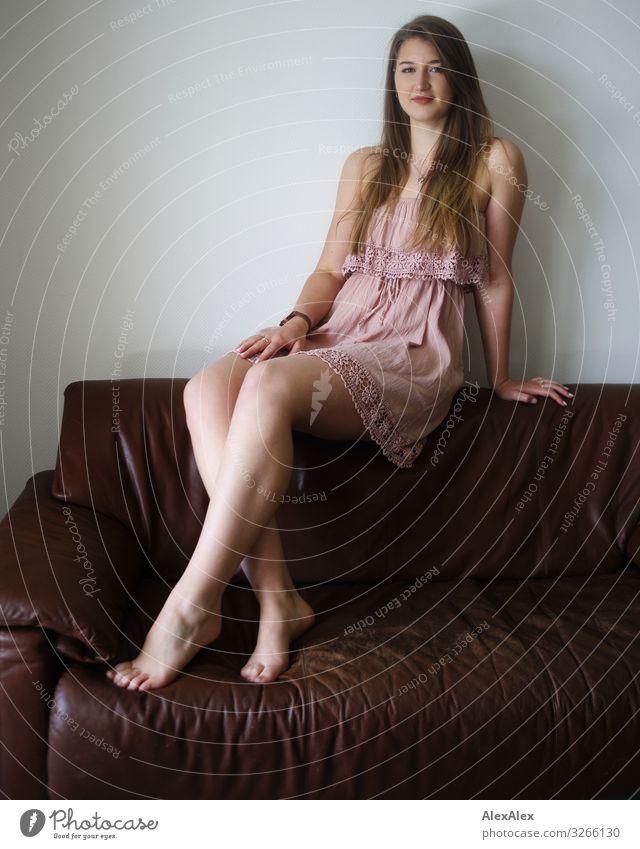 Portrait einer jungen Frau auf einer braunen Couch elegant Stil Freude schön Leben Sofa Raum Junge Frau Jugendliche Beine 18-30 Jahre Erwachsene Kleid Barfuß