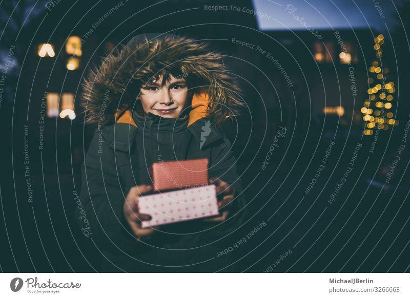 Junge mit Geschenken in Winterjacke Weihnachten & Advent Kind Mensch maskulin 1 3-8 Jahre Kindheit Freude kalt Jacke Straße Unschärfe Licht Hintergrundbild Haus