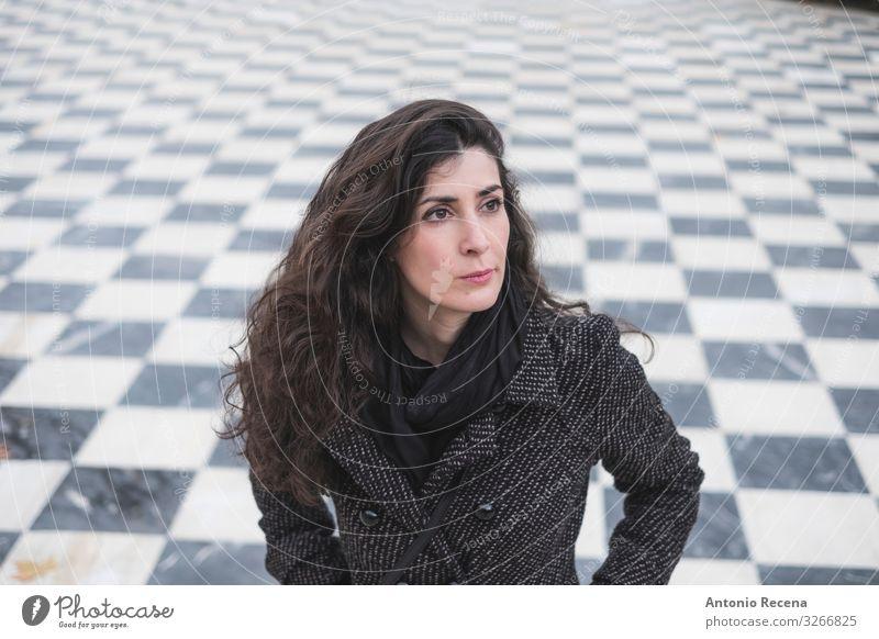 Mittelgroße erwachsene Frau, die im Park in einem ruhigen Porträt in die Kamera schaut Schach Mensch Erwachsene brünett ästhetisch verstört Fliesenboden