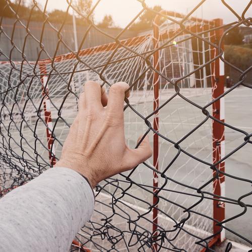 Mann, der sich von Hand einen Metallzaun schnappt. Zaun Draht Geborgenheit Schutz Mensch Finger Körperteil Arme Stahl Straße Außenaufnahme packend Freiheit
