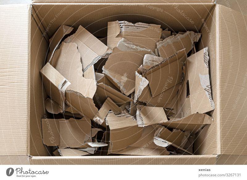 geöffneter Karton mit zerrissenen Kartonresten Papier braun Umweltverschmutzung Zerreißen Verpackungsmaterial wiederverwertbar Altpapier Kiste Müll Farbfoto