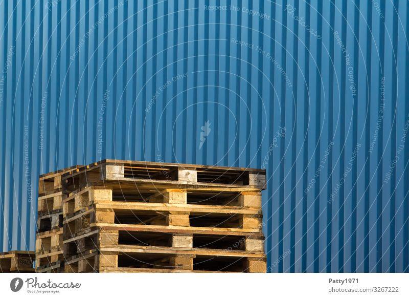 Palettenstapel vor blauer Metallwand Holz Wand Business Mauer Güterverkehr & Logistik Konkurrenz Lagerhalle Symmetrie