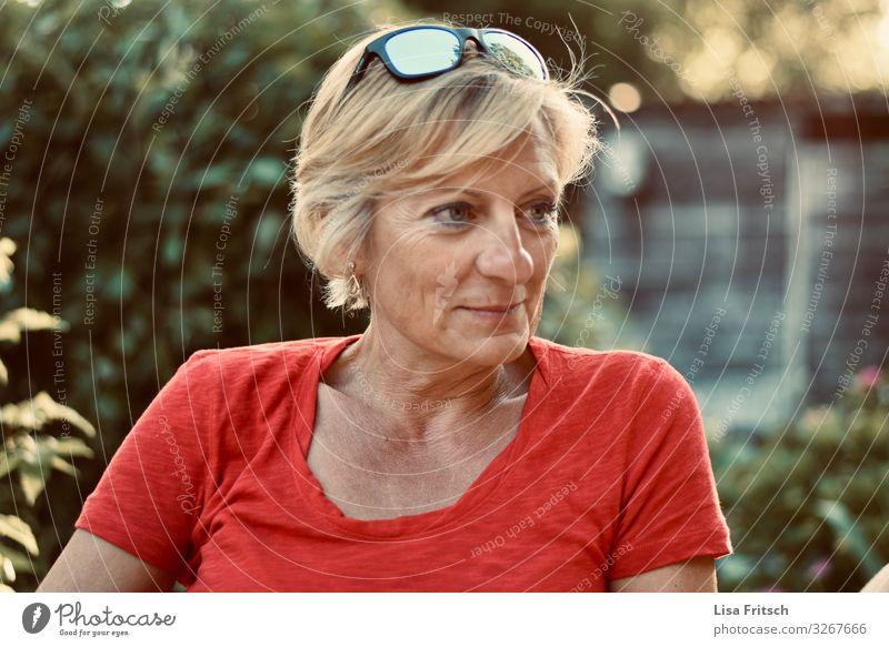 BEOBACHTEN - FRAU - ROT - SOMMER Frau Erwachsene 1 Mensch 45-60 Jahre Sommer Schönes Wetter Garten Sonnenbrille blond kurzhaarig beobachten Lächeln