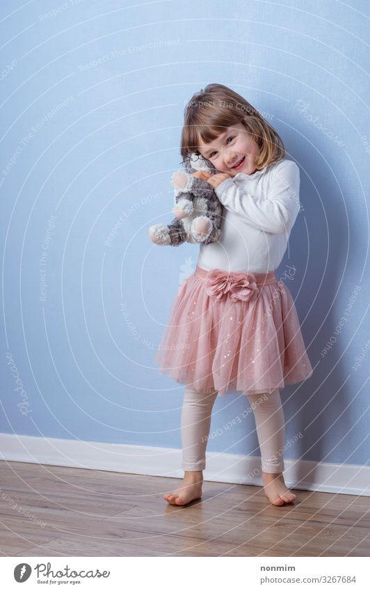 Das Mädchen umarmt ein flauschiges Katzenspielzeug, das auf dem Boden liegt. Freude Spielen Abenteuer Kind Freundschaft Spielzeug Teddybär Liebe träumen Umarmen