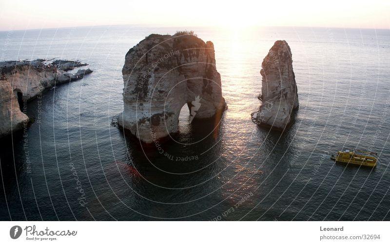 Felsen in Beirut Klippe Küste Meer Sonnenuntergang Wasserfahrzeug Durchgang Bootsfahrt Gegenlicht Felsbogen