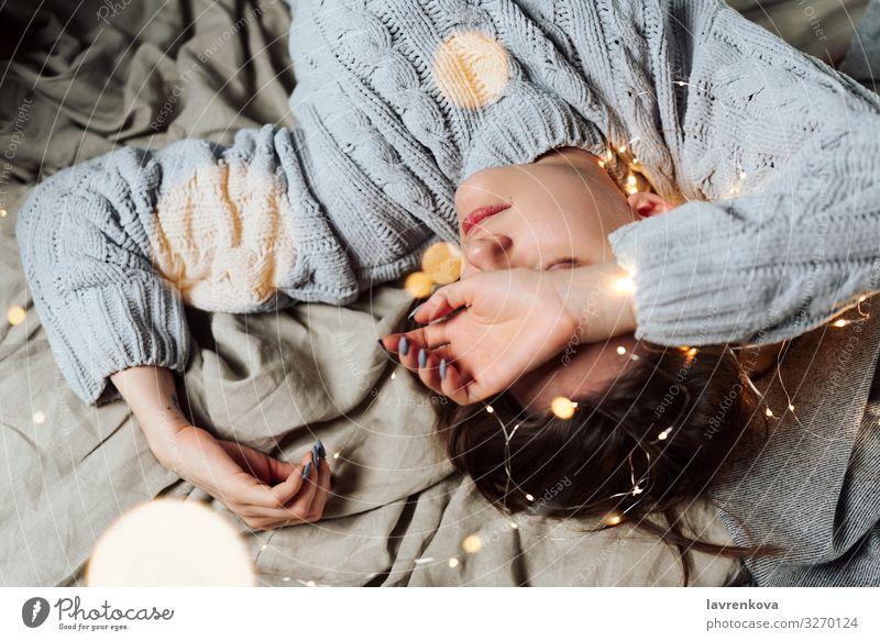 Frau im Bett liegend mit Lichterketten und Bokeh Bettwäsche Unschärfe Kaukasier Weihnachten & Advent bequem gemütlich Abend Hand Ferien & Urlaub & Reisen