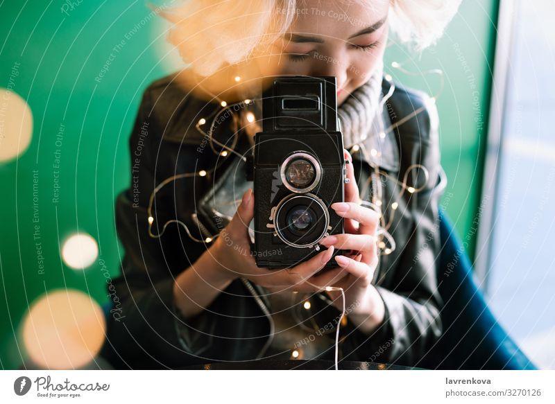 Frau mit Vintage-Filmkamera mit Lichterketten und Bokeh. altehrwürdig Asiate Café Lifestyle Filmmaterial Porträt fokussieren retro Mensch Hand Freizeit & Hobby