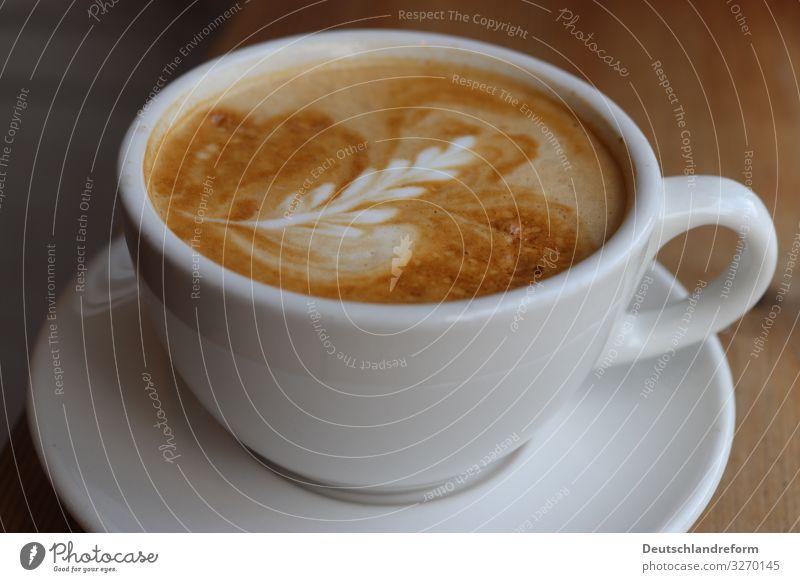 Weisse Kaffetasse auf weissem Untersetzer auf Holztisch. Kaffeeschaum mit Latte Art. Espresso Tasse Milch Schaum Kunst Barista Frühstück Innenaufnahme Koffein