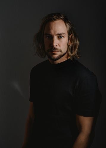 me elegant Stil maskulin Junger Mann Jugendliche 18-30 Jahre Erwachsene 30-45 Jahre Künstler T-Shirt blond langhaarig Bart Blick authentisch Coolness dunkel