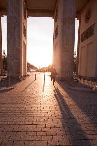 Brandenburger Tor im Sonnenuntergang mit anonymem Fahrradfahrer Leben Berlin Sehenswürdigkeit Wahrzeichen fahren Deutschland Großstadt Gegenlicht Säule Verkehr