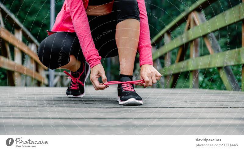 Sportlerin bindet Schnürsenkel und bereitet sich auf den Lauf vor Lifestyle Mensch Frau Erwachsene Park Krawatte Schuhe Turnschuh Fitness rosa schwarz Energie
