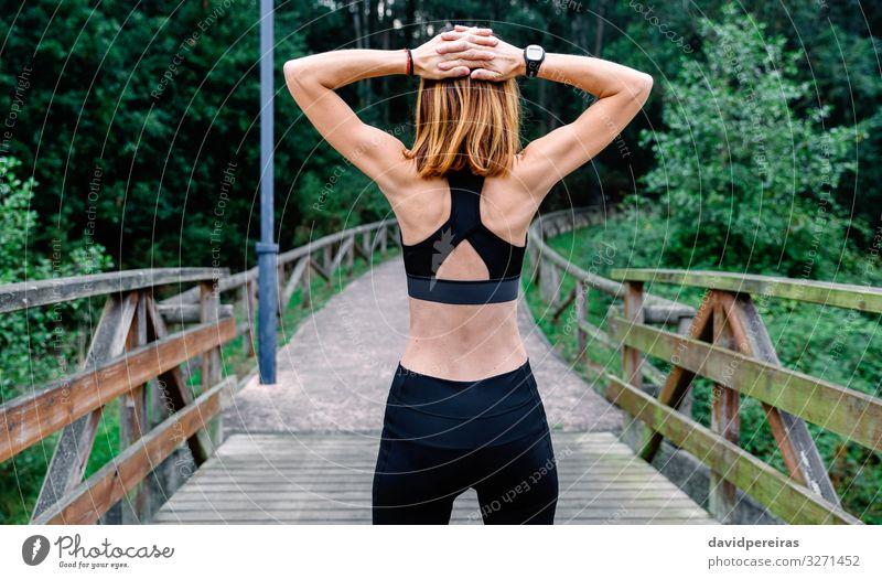 Nicht erkennbare Sportlerin, die im Freien die Arme streckt. Lifestyle Wellness Mensch Frau Erwachsene Natur Park Fitness sportlich dünn unkenntlich rückwärts