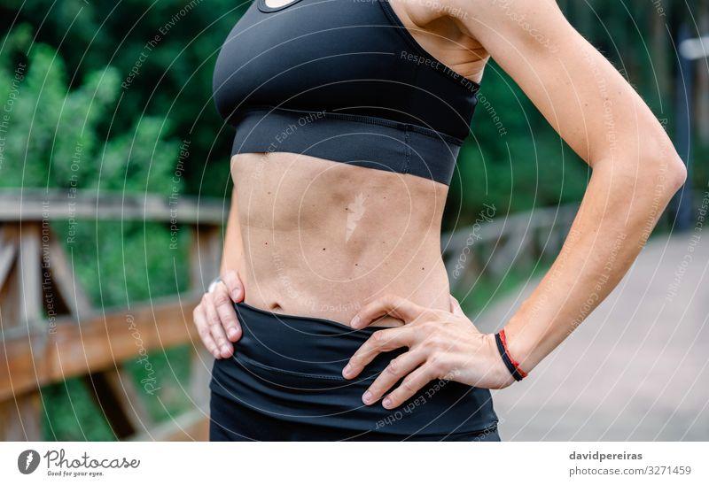 Athletin, die mit Sportbekleidung posiert. Lifestyle Mensch Frau Erwachsene Arme Hand Natur Park Fitness sportlich dünn selbstbewußt unkenntlich Bauchmuskulatur