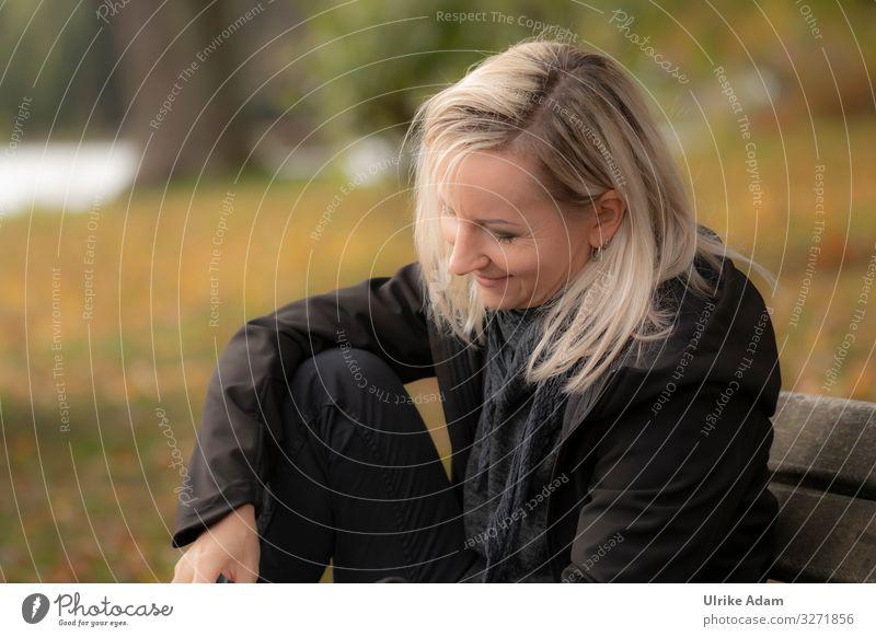 Frau sitzt entspannt mit einem Lächeln im Gesicht auf einer Bank und liest - UT Hamburg Frauengesicht lächelnd blond blondes Haar langhaarig schwarze Kleidung