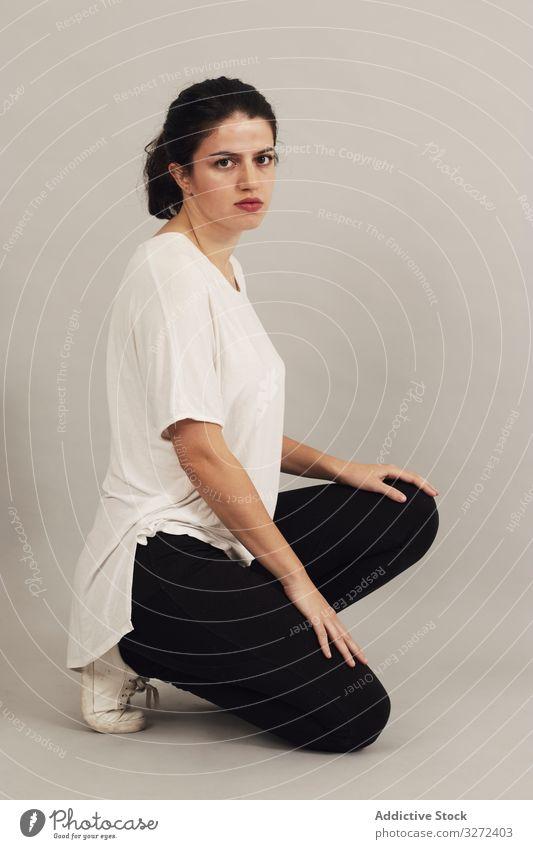 Nachdenkliche junge Frau hockt im Atelier nachdenklich Kniebeuge hocken Vorschein Persönlichkeit Individualität Teint sportlich natürlich Einfachheit ernst