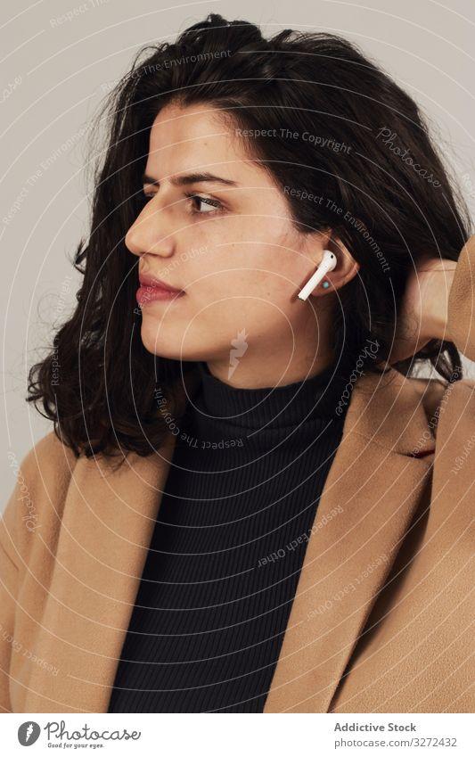 Frau mit Ohrstöpseln im Studio angezogen brünett Ort zuhören Musik genießen anhaben stereo Atelier ruhen Klang Wiedergabeliste benutzend Hobby Vergnügen tws