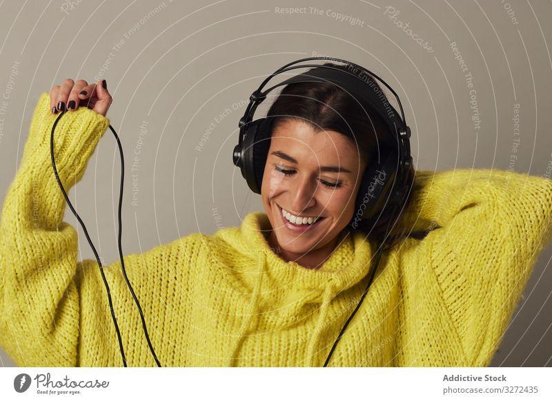Verspielte junge Frau, die im Studio Musik hört zuhören Kopfhörer anhaben gelb Pullover genießen stereo spielerisch Spaß benutzend Atelier Klang Wiedergabeliste