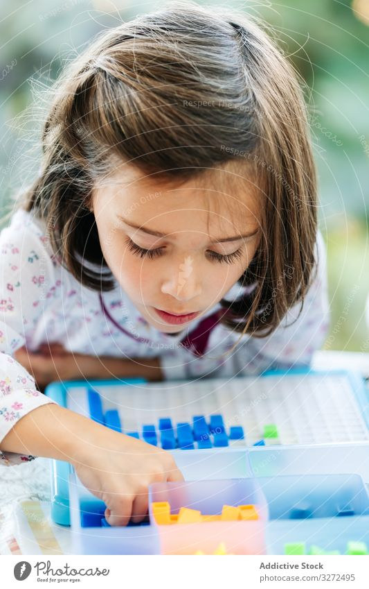 Mädchen spielt mit Mosaik-Brettspiel spielen Spiel Holzplatte kreativ fokussiert Konzentration Spielfigur farbenfroh Bildung Geduldsspiel versammeln Spaß Kind