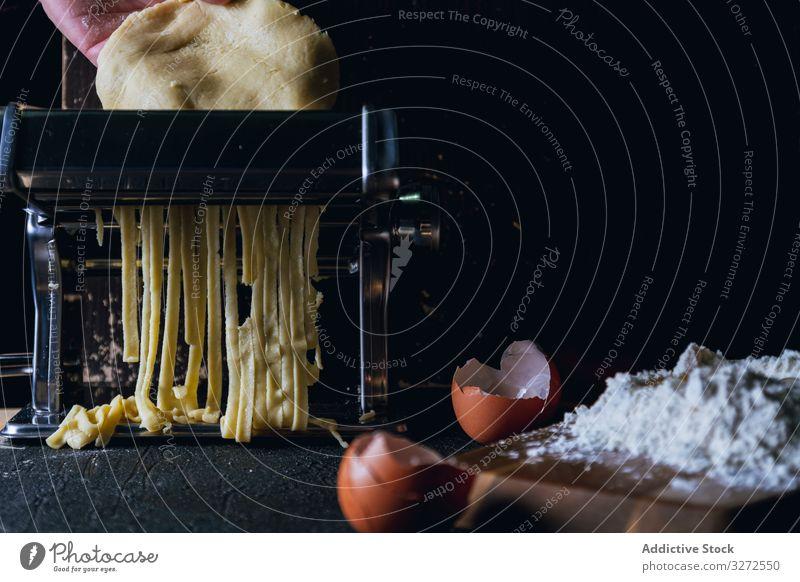 Person, die Nudeln mit der Nudelmaschine zubereitet Spätzle Maschine vorbereiten Teigwaren selbstgemacht Lebensmittel Essen zubereiten Bestandteil Schneiden