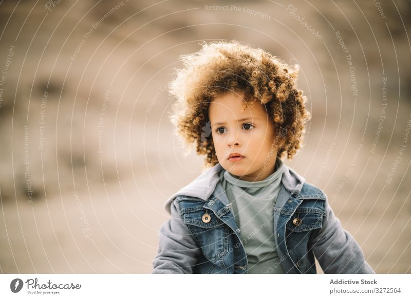 Ethnisches gelocktes Kleinkind über die Natur Kind Konzentration besinnlich bezaubernd lockig fokussiert Wind Mädchen lässig Menschliches Gesicht Porträt