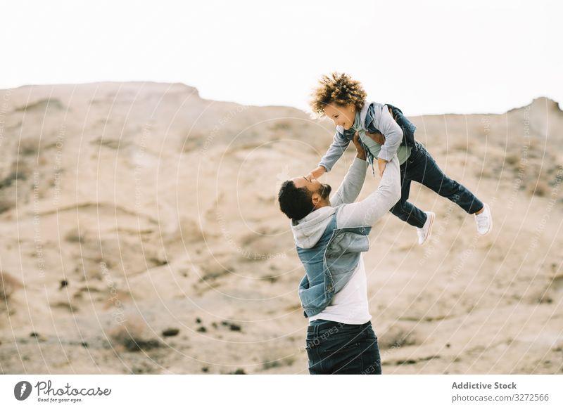 Ethnischer Vater spielt mit Kind am Boden Kleinkind spielen Spaß ruhen Sand Hügel Lächeln Eltern Glück heiter Lifestyle modern Natur Papa Mann horizontal Bonden