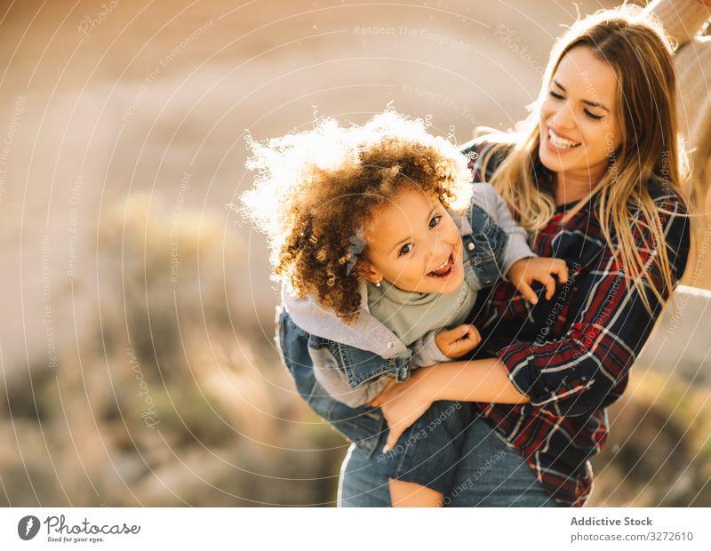 Fröhliche Frau spielt mit Kleinkind über die Natur Kind kuscheln Halt spielen Umarmen Lächeln Glück Kribbeln heiter Ausdruck krause Haare schwelgen Mutter Spaß