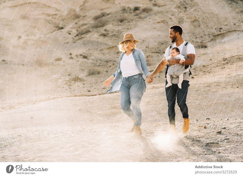 Verschiedene Eltern tanzen beim Laufen mit Baby Tanzen Familie Glück Lächeln Sand wüst Spaziergang führen Spaß Natur neugeboren heiter Lifestyle modern Kind