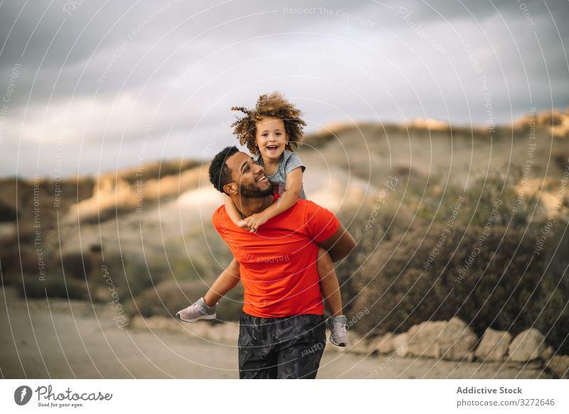 Schwarzer Vater hält Kind im Arm Kleinkind führen sportlich Lächeln spielen Spaß ruhen Eltern Glück heiter Lifestyle modern Natur Mann Bonden Liebe Angebot