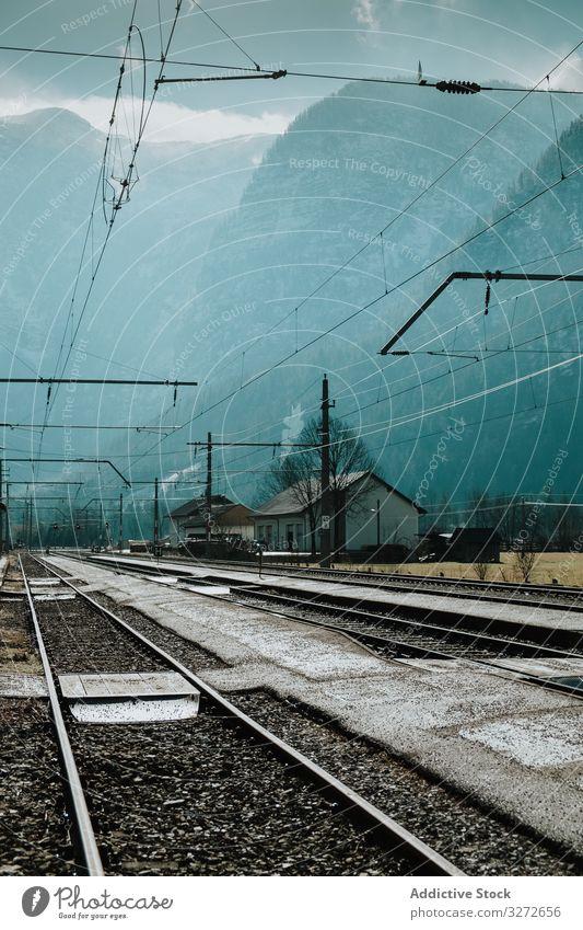 An Häusern und Bergen vorbeifahrende Eisenbahn an nebligem Tag Berge u. Gebirge elektrisch Draht Dunst Straße Station Transport Tourismus reisen Linie Struktur