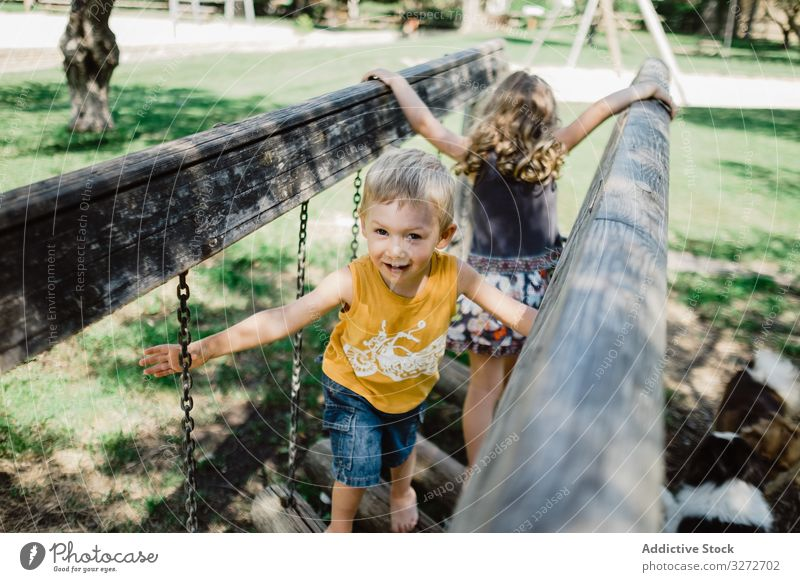 Lustige Kinder klettern an Sommertagen auf dem Spielplatz Abenteuer Spaß haben spielerisch Wiese Geschwister Klettern Baum Kindheit Natur Brücke Park aktiv