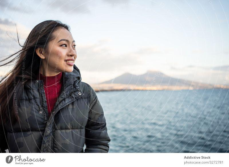 Frau im Urlaub in warmer Kleidung an der Meeresküste Meeresufer Cloud Himmel Lächeln genießen Lachen Freude reisen Tourismus sich[Akk] entspannen Wasser schön