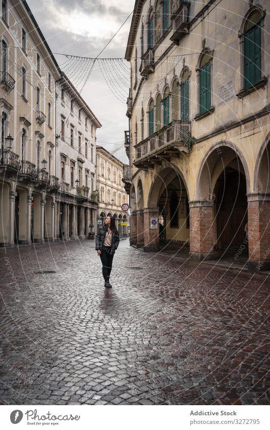 Neugierige Touristin schlendert bei bedecktem Himmel durch die Altstadt Tourismus laufen Großstadt Straße alt antik gealtert neugierig erkunden Architektur