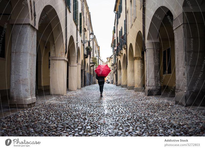 Tourist mit Regenschirm geht bei Regenwetter auf der Stadtstrasse spazieren Person Straße Großstadt laufen schlendernd erkunden Interesse nass Gebäude alt schön