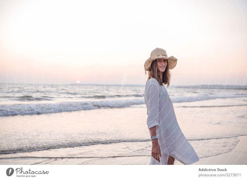 Charmante Frau in hellem weißen Kleid schaut über die Schulter in die Kamera am welligen Strand MEER reisend Lehnen Seeküste Tourismus charmant Urlaub Hut