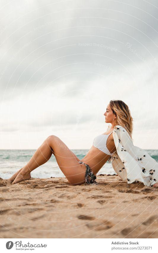 Frau ruht sich an bewölktem Tag am Sandstrand aus Spaziergang Strand MEER Wasser wolkig Himmel Urlaub Resort Wochenende Sommer Lifestyle ruhen