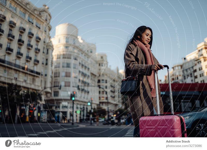 Asiatischer Tourist auf Bürgersteig in der Stadt Frau Großstadt Koffer Straße ethnisch Lächeln sonnig tagsüber besuchen asiatisch Gepäck reisen Ausflug jung