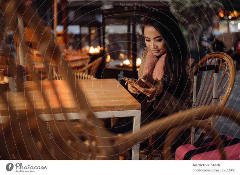 Asiatischer Reisender benutzt Smartphone im Cafe Frau Café benutzend Tourist Koffer ethnisch Abend Großstadt urban asiatisch Browsen soziale Netzwerke lässig