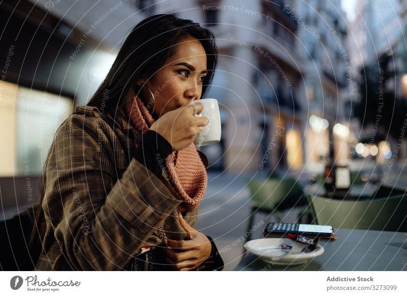 Asiatin genießt Heißgetränk in Straßencafé Frau Café trinken Abend Großstadt urban schlürfen Tasse ethnisch jung stylisch trendy Kaffee Tee Getränk heiß