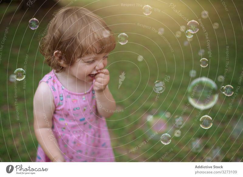 Fröhliches Mädchen spielt mit bunten Blasen im Gras Seife Kindheit freudig Spaß bezaubernd Spielen heiter Park spielerisch Genuss Aktion nass wenig Bewegung