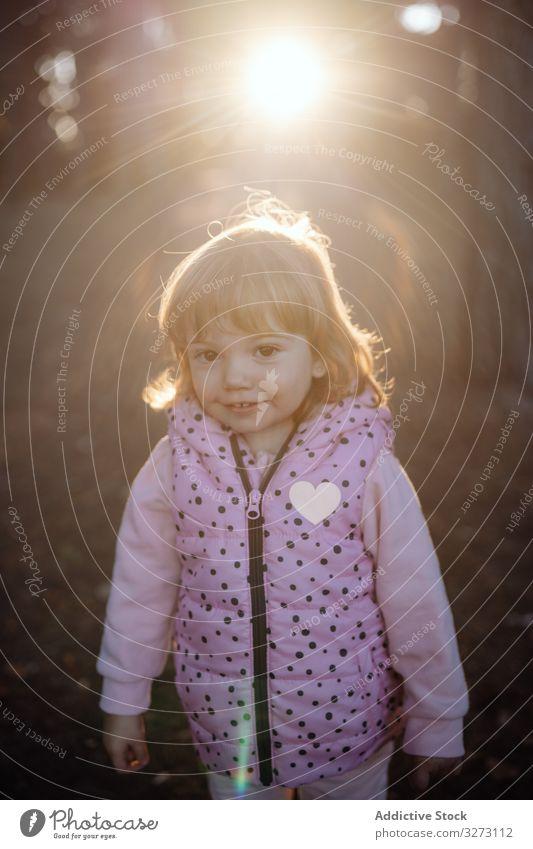Bezauberndes niedliches Mädchen in Jacke schaut in die Kamera im Park Weste Herz heiter Kindheit aktiv Spaß Sonnenlicht Natur Freude Aktivität Genuss