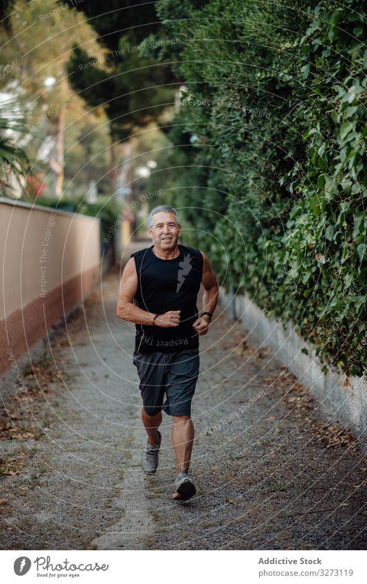 Alter Mann in guter Verfassung rennt auf Straße entlang Pflanzenzaun sportlich Joggen älter reif alt Form Training Läufer Athlet Fitness Großstadt passen